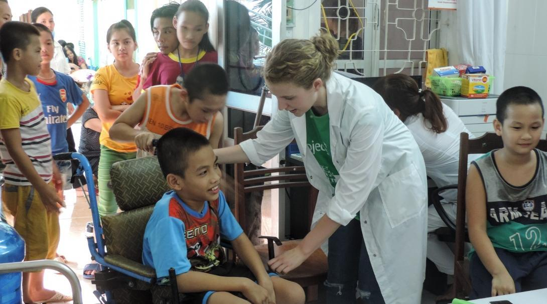 An intern is helping a young disabled boy during a medical outreach whilst she undertakes her nursing internship in Vietnam with Projects Abroad.